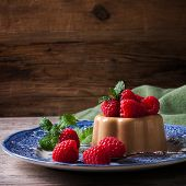 foto of dessert plate  - Italian dessert coffee panna cotta served on a blue plate with raspberries and fresh mint on vintage wooden bckground - JPG