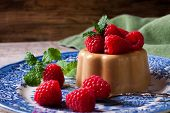 image of dessert plate  - Italian dessert coffee panna cotta served on a blue plate with raspberries and fresh mint on vintage wooden bckground - JPG