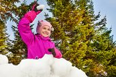 picture of snowball-fight  - Girl ready to throw snowball while standing behind the snow wall with fir forest on the background during beautiful winter day - JPG