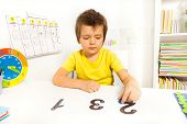 picture of numbers counting  - Boy putting blue coins on the numbers learning to count during Applied Behavior Analysis ABA sitting at the table indoors - JPG
