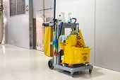 pic of slip hazard  - Yellow mop bucket and set of cleaning equipment in the airport - JPG
