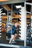 foto of squatting  - Young man squatting with barbell in the gym - JPG