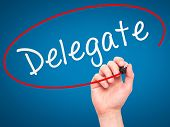stock photo of mandate  - Man Hand writing Delegate black marker on visual screen - JPG