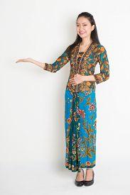 stock photo of southeast  - Full length portrait of Southeast Asian woman in batik dress hand holding something standing on plain background - JPG
