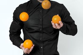 picture of juggling  - Man in black shirt juggling with four oranges - JPG