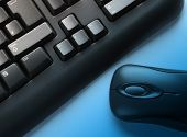 Computer keyboard and mouse. Blue lighting effect applied.