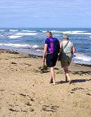 Elderly couple walking on sandy beach on sunny day