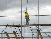 stock photo of scaffolding  - Closeup of construction worker assembling scaffold on building site - JPG