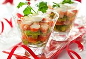 Crab salad with avocado in two glasses . Served on a Christmas table.