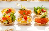 Christmas starter platter with appetizers.Tartlets with three different fillings(vegetable salad,cra