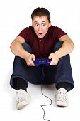 Young Man Sitting On Floor, Holding Joystick And Playing Console Games, Surprised Face, Isolated