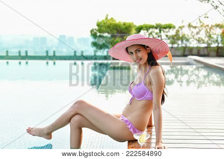 poster of Swimsuit Concept. Beautiful girl wearing pink swimsuit. Beautiful girl in swimwear is relaxing at the swimming pool. Independent living sexy woman at the city center pool.