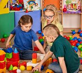 Children building blocks in kindergarten. Group kids playing toy on floor. Interior preschool. Kid i poster