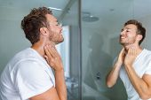 Man putting after shave perfume lotion or skin care cream for sensitive skin after shaving beard loo poster