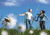 couple having fun in a meadow full of dandelions