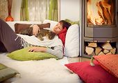 stock photo of fondling  - woman with a cat relaxing beside a fireplace - JPG