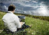 empresario con el portátil en un campo con nubes oscuras