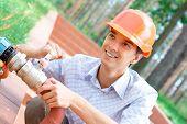 Smiling manual worker repairing a pipe