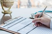 Doctor Writing On Medical Health Care Record, Patients Discharge, Or Prescription Form Paperwork In  poster