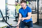 People in gym doing sport in functional fitness training with battle rope poster