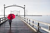 Woman holding a red umbrella walking on a rainy day on the pier in White Rock, British Columbia, Can poster