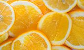 Bright Orange Background From Slices Of Juicy Oranges. Orange Whole.orange Haif. Oranges Slice poster