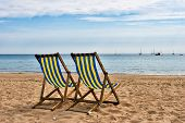 Two deckchairs on a sandy beach