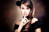 beautiful young woman gesturing silence, studio shot
