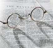 picture of revelation  - Old fashioned round reading glasses laying on a page from the bible on the revelation with strong shadow and out of focus areas - JPG