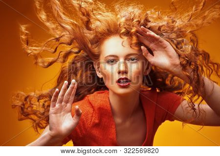 poster of Long curly red hair. Portrait of a beautiful fashion girl with magnificent long hair in motion. Yell