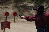 pic of wild west  - A wild west cowboy shoots his pistol at targets - JPG