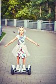 Girl  Rides Whirl On A Hoverboard Over Park Paths poster