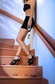stock photo of mini-skirt  - Woman in bra and mini skirt standing at stairway - JPG