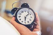 Man Hand Holding Alarm Clock For Wake Up At 7.00 A.m. In Morning Wake Up On Time With Light Effect I poster