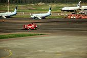 Fire Truck On The Runway Near The Aircraft. Airport Rescue Service. Firefighters And Fire Department poster