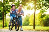 Happy Family Mother Teaches Child Daughter To Ride A Bike In The Park In Nature poster