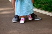 Dad Teaches Daughter To Walk. Happy Dad And Daughter. Dad With A One-year-old Daughter In A Dress Ar poster