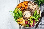 Buddha Bowl With Tofu, Avocado, Rice, Seedlings, Sweet Potato And Tahini Dressing. Vegan Food Concep poster