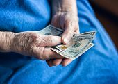 Dollar Bills In The Hands Of An Elderly Man. A Pensioner Holds Money In His Hands. Elderly Man Holdi poster
