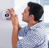 Man installing surveillance CCTV cameras at home poster