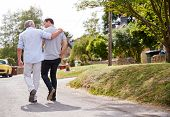 Rear View Of Senior Father With Adult Son Talking As They Walk Along Country Road Together poster