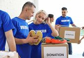 Team Of Volunteers Collecting Donations In Boxes Indoors poster