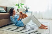 Playing With Cat At Home. Young Woman Sitting On Carpet And Hugging Pet. poster
