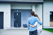 Couple in front of one-family house in modern residential area poster