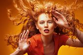 Long curly red hair. Portrait of a beautiful fashion girl with magnificent long hair in motion. Yell poster