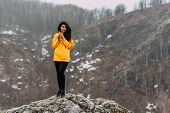Traveler Holding A Mug Of Hot Tea In The Mountains. Woman In Sportswear In The Mountains. Climb To T poster