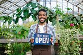 African American Man Is Standing In Greenhouse With We Are Open Sign Smiling Looking At Camera Welco poster