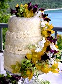 stock photo of tropical food  - Tropical wedding cake surrounded by cascading colorful native flowers - JPG