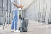 Start Of Travel. Male Tourist With Luggage And Boarding Documents Waiting For Flight At Airport, Fre poster