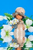 Little flower girl on blue background with white decoration flowers and water reflection